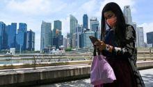 امرأة مستغرقة في تفحص الموبايل أمام عدد من ناطحات السحاب في سنغافورة