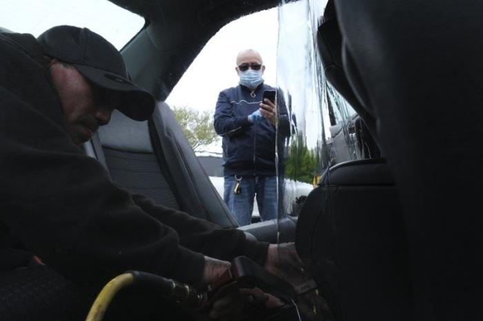 سائق لشركة أوبر يتابع عملية وضع حاجز بلاستك في سيارته لعزل السائق عن الركاب للوقاية من فيروس كورونا