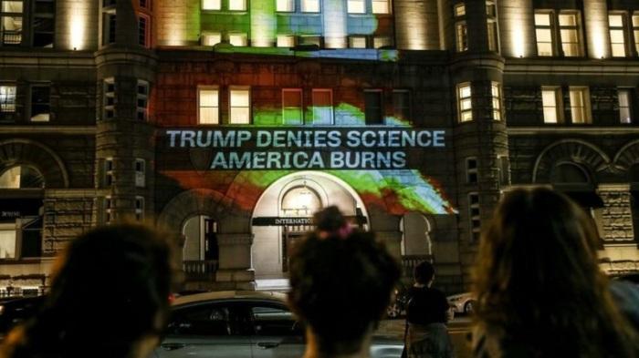 متظاهرون يعترضون على سياسات المناخ للرئيس ترامب ويعرضون رسالتهم على أحد فنادقه