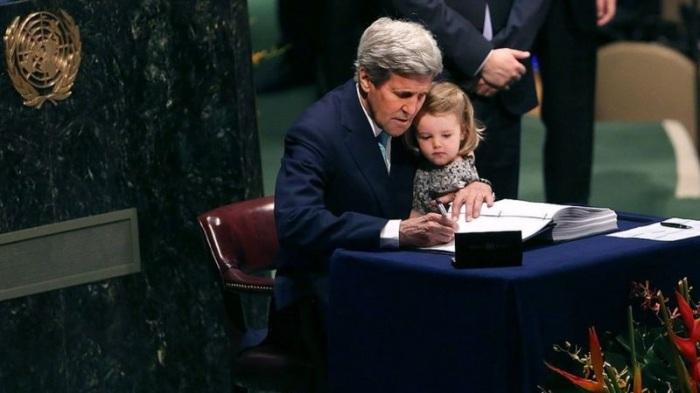 وزير الخارجية السابق جون كيري يحمل حفيدته وهو يوقع اتفاقية باريس في الأمم المتحدة