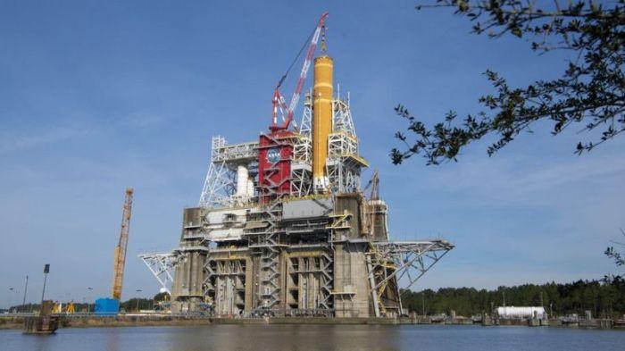 يتم اختبار المرحلة الأساسية من صاروخ ناسا العملاق SLS (باللون البرتقالي) على منصة الاختبار