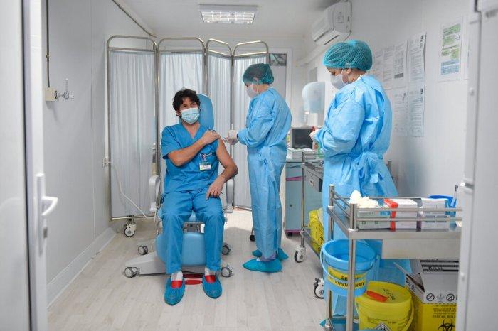 أحد أعضاء الفرق الطبية يتلقي لقاح كورونا في بوخاريست عاصمة رومانيا