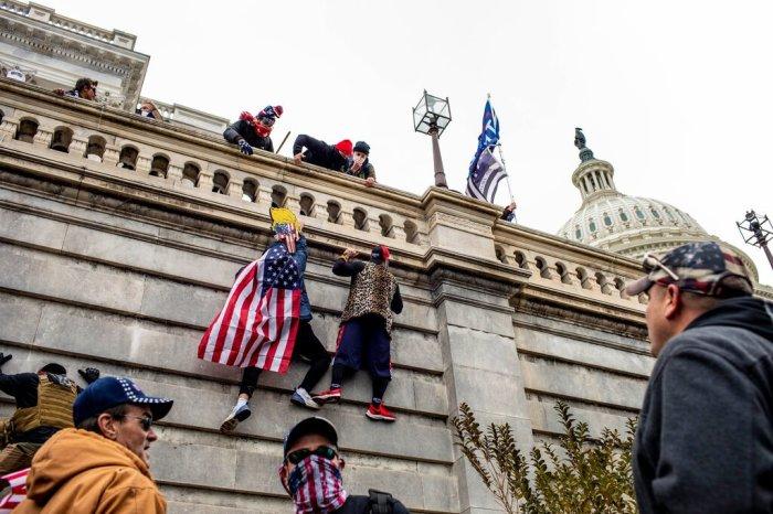 أنصار الرئيس دونالد ترامب يتسلقون جانب مبنى الكابيتول يوم الأربعاء 6 يناير 2021 لدخوله احتجاجًا علي نتائج الإنتخابات الرئاسية الأمريكية 2020