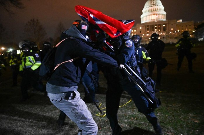 أحد مؤيدي الرئيس ترامب يشتبك مع أحد رجال شرطة مكافحة الشغب خارج مبنى الكابيتول مساء الأربعاء 6 يناير 2021