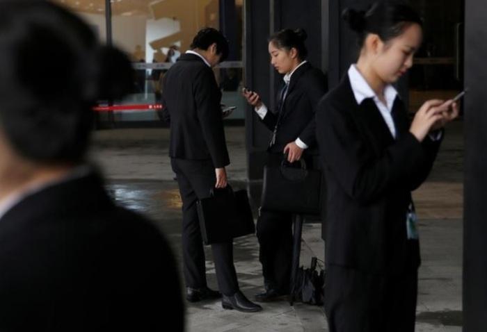 أشخاص يفحصون هواتفهم خلال المؤتمر العالمي السنوي الثالث للإنترنت في مدينة وزهان بمقاطعة زيهجينج، الصين