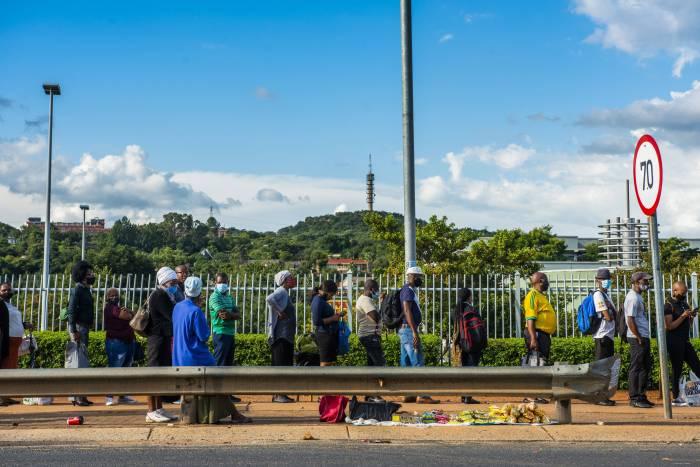 ركاب يرتدون كمامات طبية ينتظرون سيارات الأجرة في بريتوريا، جنوب إفريقيا، في 8 فبراير 2021