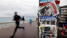 رجل يركض أمام رف أخبار يعرض نسخًا من الصحف الفرنسية في بروميناد ديزونجليه في نيس