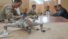 طائرة مسيرة صغيرة تابعة لداعش، استولت عليها الشرطة العراقية، موضوعة على طاولة في اجتماع لتبادل المعلومات الاستخبارية في مطار القيارة الغربي بالعراق