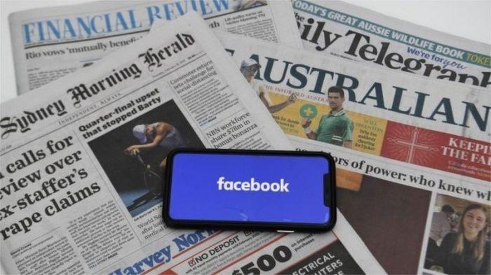 شعار فيسبوك علي شاشة موبايل خلف مجموعة من الصحف الأسترالية
