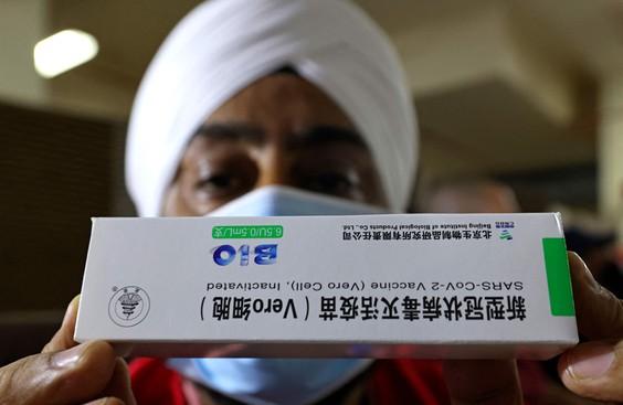 عامل رعاية صحية يحمل صندوقًا من لقاح سينوفارم الصيني كوفيد-19 أثناء التطعيم في (معبد السيخ) في دبي في 28 فبراير 2021