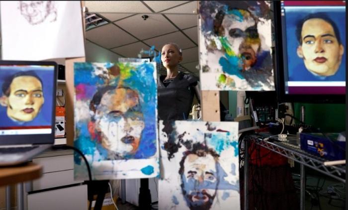 الروبوت الفنانة صوفيا تقف بين أعمالها الفنية قبل بيعها في المزاد، الصورة تم التقاطها يوم الثلاثاء 16 مارس 2021