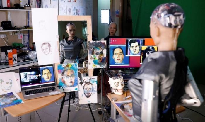 الفنانة الروبوت صوفيا تقف بأعتزاز أمام أعمالها الفنية
