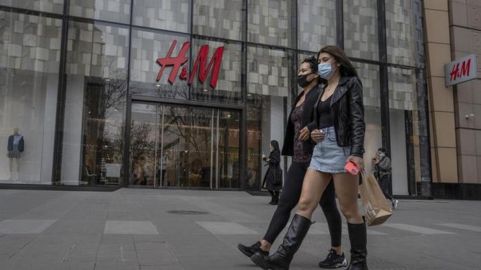 نساء يمشين بجوار متجر ملابس H&M في منطقة تسوق في بكين ، الصين