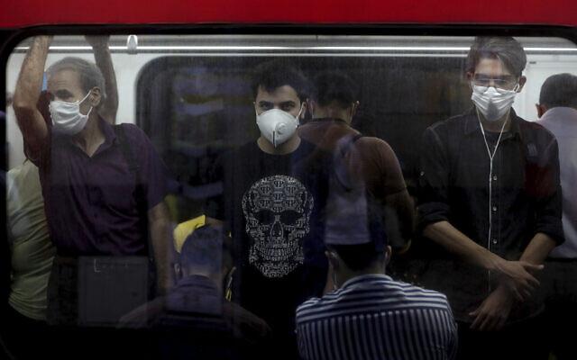 ركاب يرتدون أقنعة واقية للوجه للمساعدة في منع انتشار فيروس كورونا يقفون داخل قطار في طهران، إيران، 8 يوليو 2020